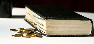 A Bible and some coins next to it signifying WICC's program Fellowship of the Least Coin