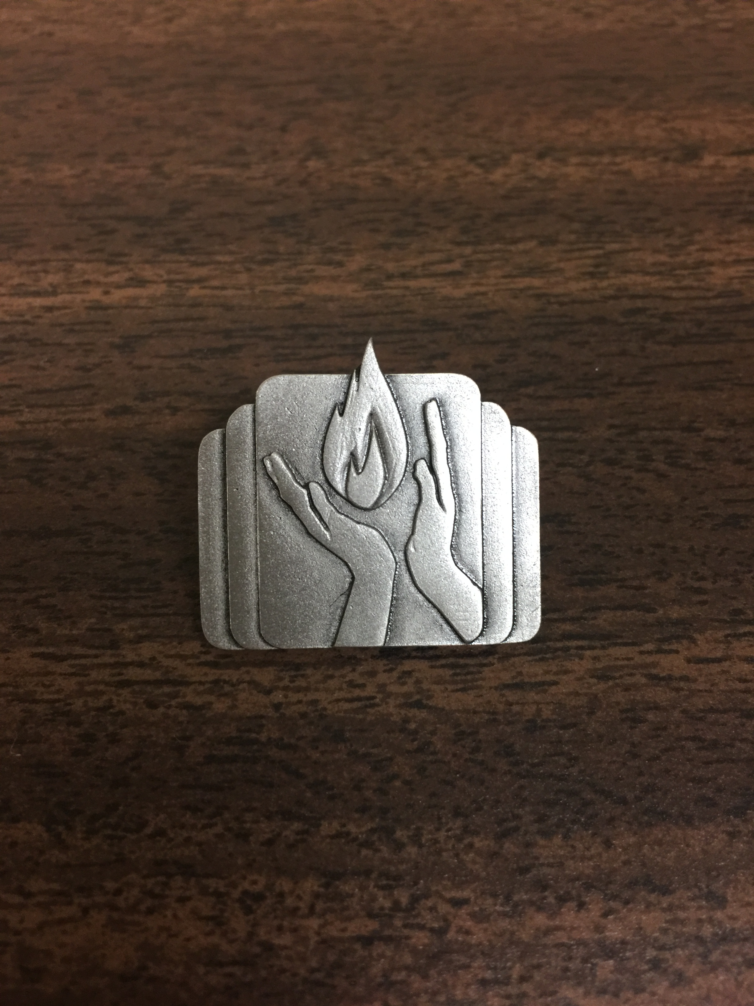 WICC pin with a flame in hands