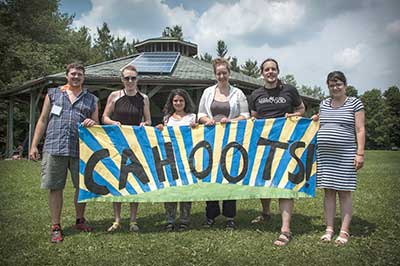 Cahoots organizers posing with big banner for WICC
